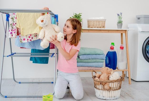 Маленькая девочка висит плюшевый мишка на сушилке с булавкой в светлой прачечной