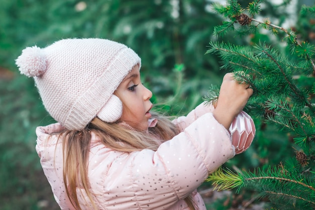 A little girl hangs a christmas toy on a tree in the park.