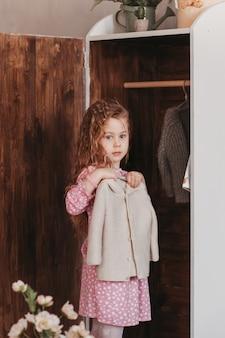 Маленькая девочка вешает одежду в шкафу