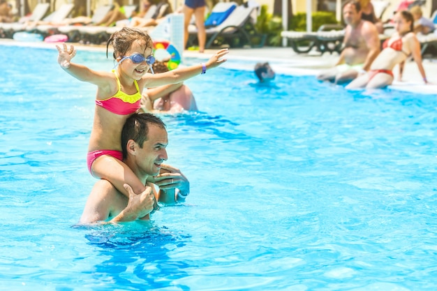 Little girl and happy dad having fun together in outdoors swimming pool