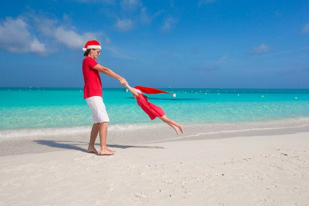 Little girl and happy dad in santa hat having fun during summer vacation