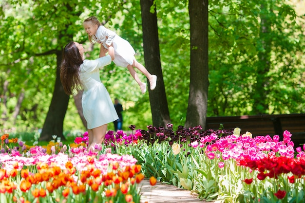 Little girl and happy mother enjoying warm day in bloomig tulip garden