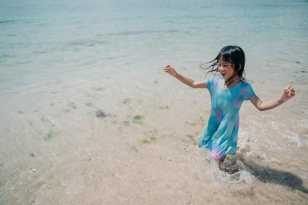 彼女の足に来る波を感じて幸せな少女