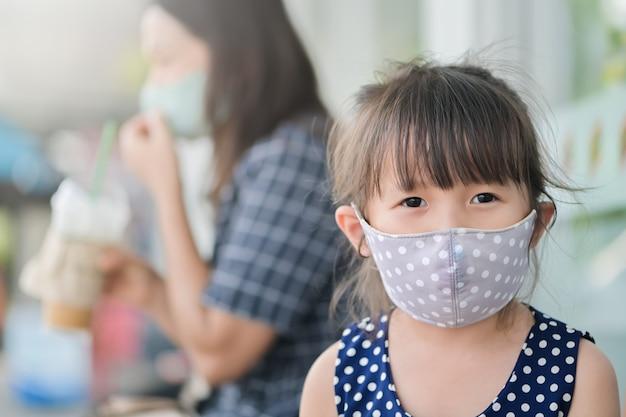 Маленькая девочка носит тканевую маску на носу, чтобы защитить себя от болезней или загрязнения воздуха коронавирусом во время активного отдыха