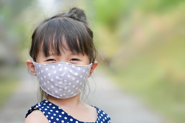 Маленькая девочка носит тканевую маску на носу для безопасного активного отдыха, болезни коронавирус или загрязнения воздуха