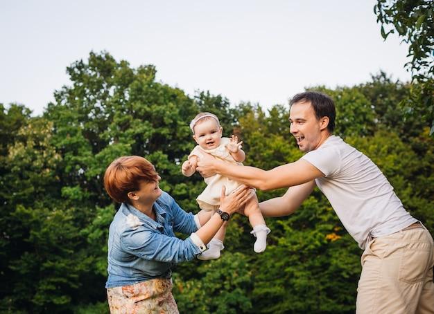 Маленькая девочка веселится, а родители крутят ее