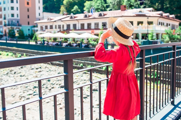 Little girl at hat on the embankment of a mountain river in a european city.
