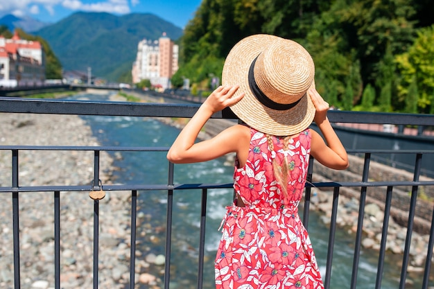 Little girl at hat on the embankment of a mountain river in a european city,