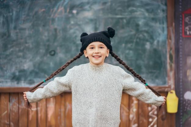 Bambina in un cappello in posa sullo sfondo della lavagna della scuola