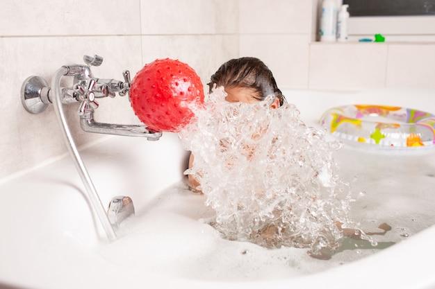 Маленькая девочка веселится в ванне и играет в надувной красный мяч