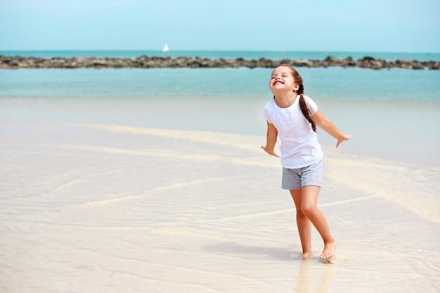 Маленькая девочка развлекается на пляже
