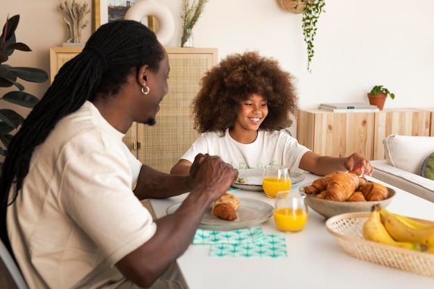 Bambina che fa colazione con suo padre