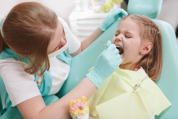 Little girl having dental checkup by professional dentist