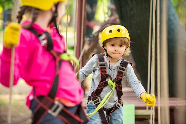 모험 공원에서 즐거운 시간을 보내는 어린 소녀 공원에서 나무를 오르는 아이 saf 등반에 귀여운 소녀...
