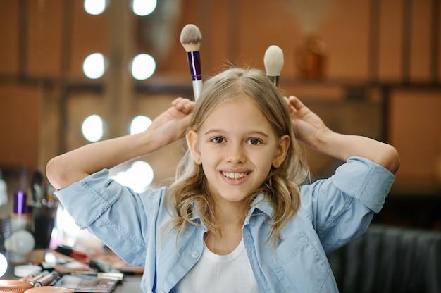 메이크업 살롱에서 거울에 재미 어린 소녀