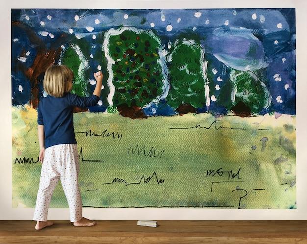 Little girl having fun drawing on a wall
