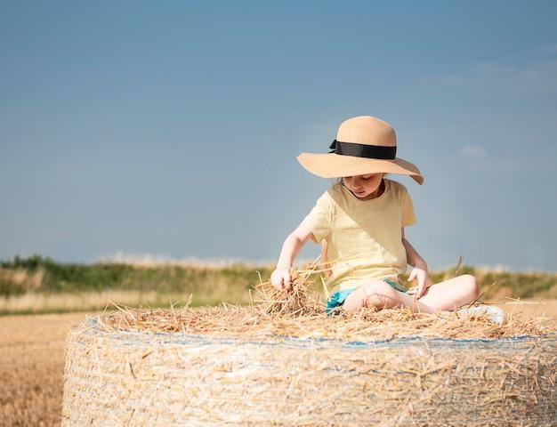 여름날 밀밭에서 즐거운 시간을 보내는 어린 소녀. 수확 시간 동안 건초 베일 필드에서 노는 아이.