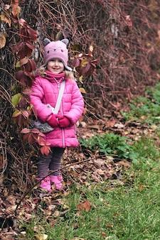 Маленькая девочка с удовольствием в красивом парке с сухими желтыми и красными листьями. осенняя семейная прогулка в лесу
