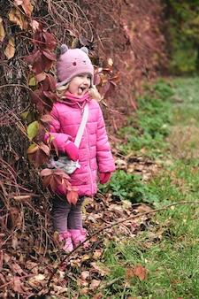 Маленькая девочка с удовольствием в красивом парке с сухими желтыми и красными листьями осенняя семейная прогулка в лесу
