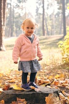 Маленькая девочка с удовольствием в красивом парке с сухими желтыми и красными листьями. осенняя семейная прогулка в лесу.