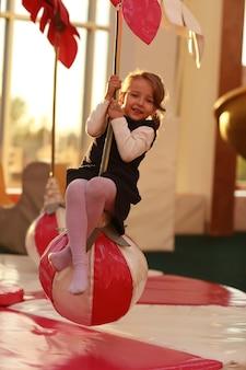 Маленькая девочка с удовольствием в детской игровой. девушка катается на детской карусели в виде пальмы. центр отдыха и развлечений.
