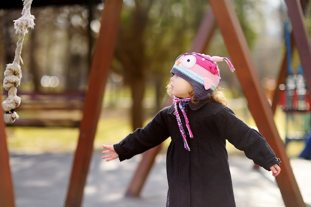 Little girl having fun on outdoor playground on spring or autumn day