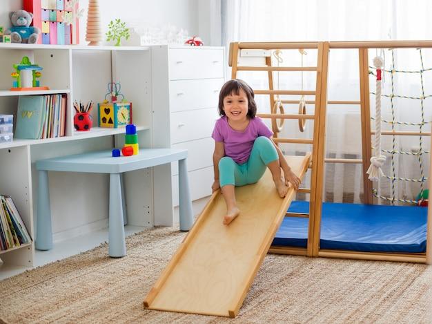 木製の家のスポーツゲームの複雑な階段でジェットコースターに乗って楽しんでいる小さな女の子