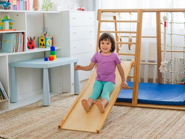 Маленькая девочка с удовольствием катается на американских горках на деревянном спортивном игровом комплексе по лестнице