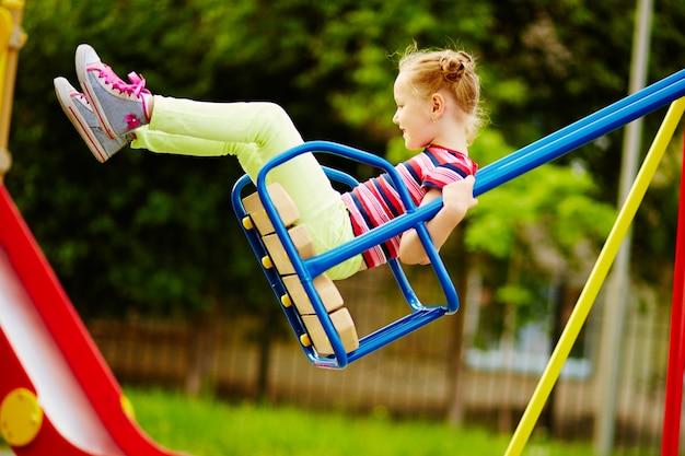 Bambina che ha divertimento su un'oscillazione all'aperto