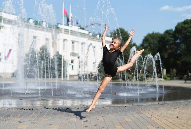 Little girl having fun at water fountain