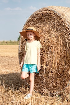 小女孩获得乐趣在麦田在一个夏日。在收获时间的干草大包领域使用孩子。