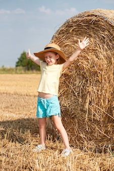 Little girl having fun in a wheat field on a summer day. child playing at hay bale field during harvest time.