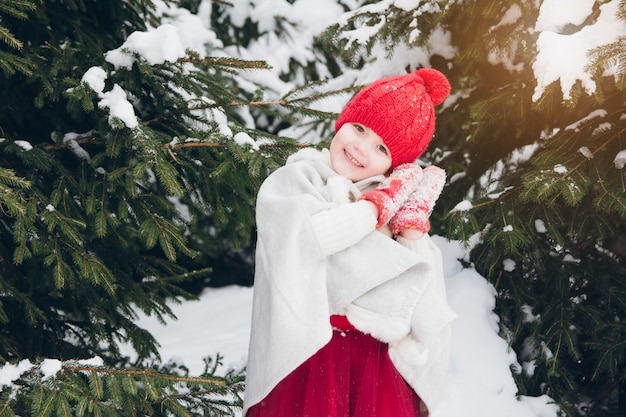 Little girl having fun in the winter forest