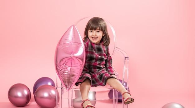 風船と紙吹雪を楽しんでいる小さな女の子。お祝いと楽しみのコンセプト。