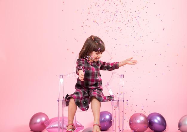 紙吹雪を楽しんでいる小さな女の子。お祝いと楽しみのコンセプト。