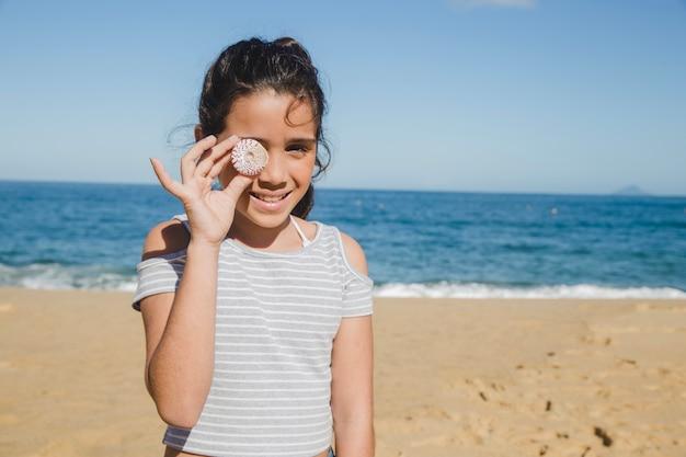 Little girl having fun with a seashell