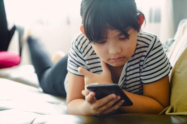 自宅でスマートフォンを使用して楽しんでいる小さな女の子