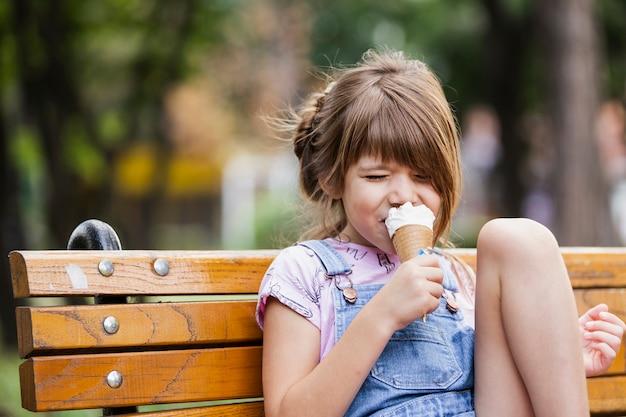 Маленькая девочка с мороженым, сидя на скамейке