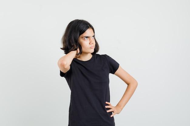 어린 소녀는 검은 색 티셔츠에 목에 통증이 있고 불편한 전면보기를보고 있습니다.