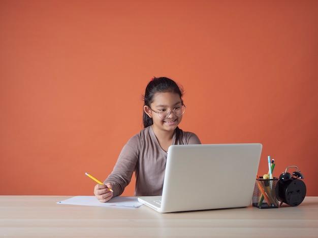 Маленькая девочка, имеющая онлайн-обучение с ноутбуком дома.