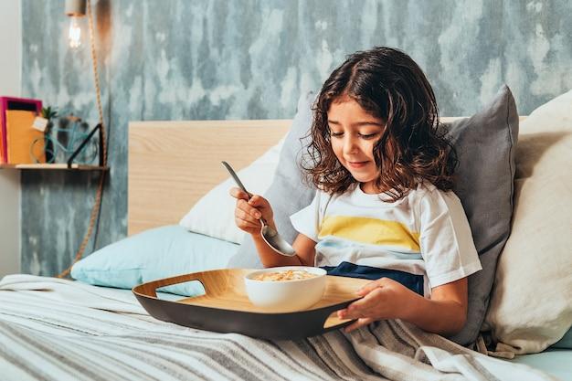 Маленькая девочка, завтракающая в воскресенье в постели