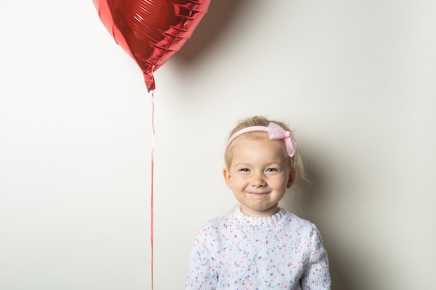Little girl and heart air balloon on a light background. concept for valentine's day, birthday. banner.