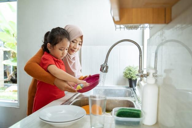 Маленькая девочка помогает матери в мытье посуды