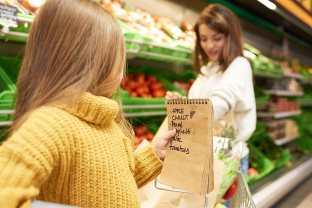 Маленькая девочка помогает покупать продукты