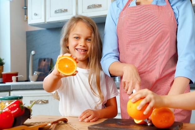 Маленькая девочка помогает маме резать апельсины