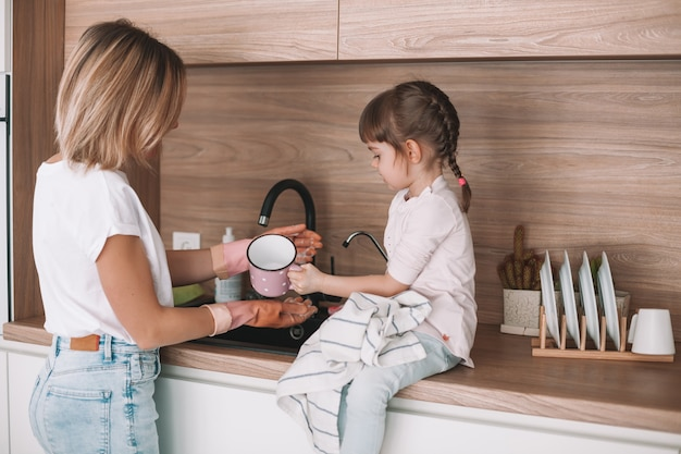 Little girl helping her mother with dishwashing in the kitchen. woman is washing the dishes, her daughter wiping the cup off with a towel.