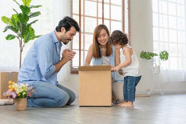 Маленькая девочка помогает родителям упаковывать коробки для переезда в новый дом