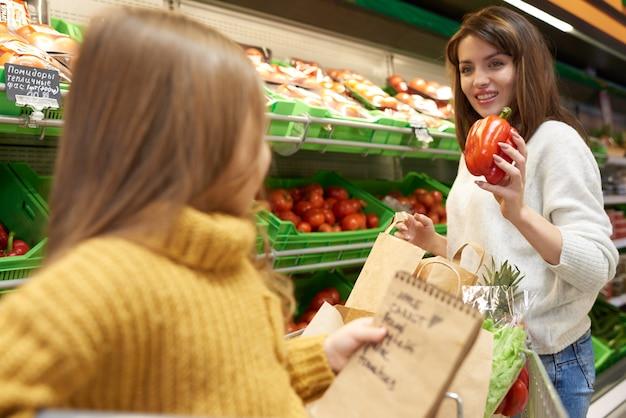 Маленькая девочка помогает маме с покупками