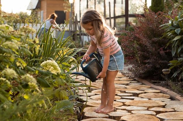 어린 소녀는 여름에 장난감 물을 깡통에서 정원에 있는 꽃에 물을 주는 어머니를 돕습니다