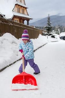 少女は両親が庭から雪をきれいにするのに役立ちます
